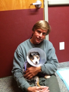 Bo holding Ivy at our vet during one of the splint-change visits, about 10 weeks.